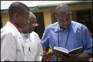Program Manager Ildephonse Munyarugero consults with staff