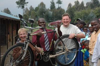 Charlene Jendry, PIC coordinator, and co-founder Jeff Ramsey (right) give the Bisate School headmaster bicycles for teachers