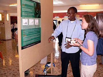 Felix Ndagijimana displays his poster to Dr. Martha Robbins