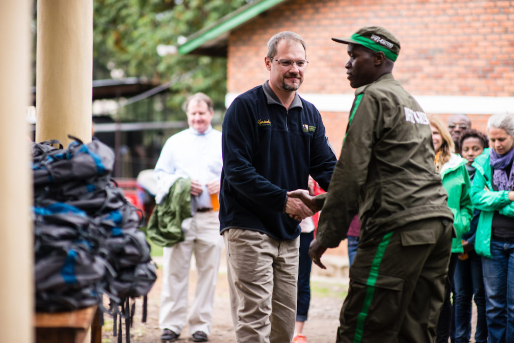 Fossey Fund board chair Dwight Scott, center, hands out new equipment to Karisoke trackers